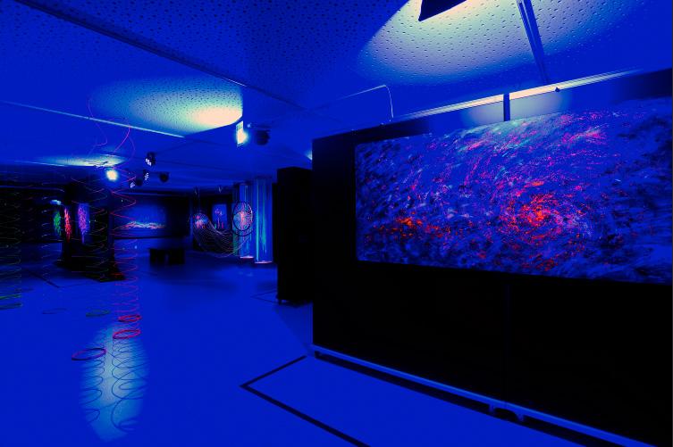 """Vista da exposição """"Luminescências [...]"""", com a obra (à direita) com projeção de luz azul"""